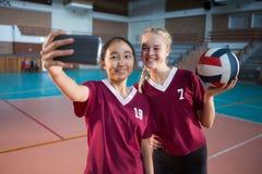 Jugadores femeninos sonrientes que toman el selfie con el teléfono móvil Foto de archivo