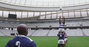 Jugadores masculinos del rugbi que juegan el partido del rugbi en el estadio 4k almacen de metraje de vídeo