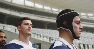 Jugadores masculinos del rugbi que se colocan en el estadio 4k metrajes