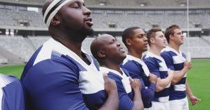 Jugadores masculinos del rugbi que toman compromiso junto en el estadio 4k almacen de metraje de vídeo