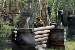 Jugadores que juegan en el juego del bosque en Paintball imagen de archivo libre de regalías