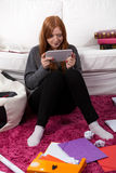 Jugando al juego en la tableta en lugar de otro que aprende Foto de archivo