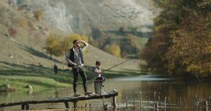 Jugando al muchacho con una caña de pescar grande, él está con su papá en la pesca al lado del lago almacen de metraje de vídeo