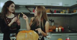 Jugando dos señoras delante de la cámara en Halloween van de fiesta en casa, llevando a cabo algo disponible, ellas están sonrien almacen de metraje de vídeo