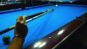 Jugando el billar - un tiro de un hombre que juega el billar en una mesa de billar azul almacen de video