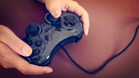 Jugando a juegos con Joy Stick análoga a disposición Foto de archivo