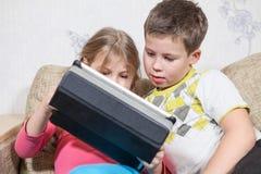 Jugando a los niños que se sientan en el sofá junto, sosteniendo la PC de la tableta con el juego interesante Imagen de archivo