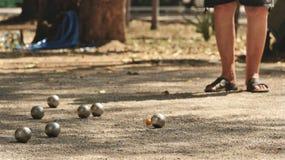 Jugando Petanque en el parque - bolas de metal y bola de madera anaranjada en yarda de la roca con un hombre que se coloca en el  fotografía de archivo