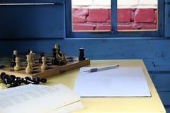 Jugar a ajedrez en la casa Lectura de un libro Entradas del cuaderno Foto de archivo libre de regalías
