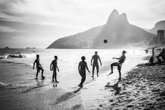 Jugar al balompié en la playa Imágenes de archivo libres de regalías