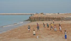 Jugar al balompié en la playa Fotos de archivo libres de regalías