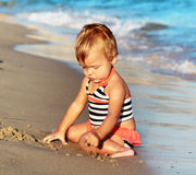 Jugar al bebé en una playa de la arena Fotografía de archivo libre de regalías