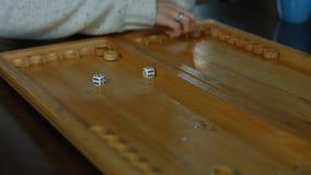 Jugar a backgammon en una tabla de madera con los dados almacen de video
