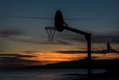 Jugar baloncesto en la puesta del sol fotos de archivo libres de regalías