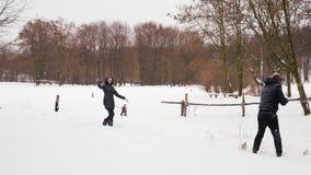 Jugar bolas de nieve en el bosque del individuo indio con una muchacha almacen de metraje de vídeo
