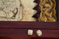 Jugar dados en un tablero del juego Fotos de archivo libres de regalías