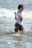 Jugar de funcionamiento del niño joven feliz del muchacho y divertirse en la resaca y las ondas de una playa soleada arenosa Fotos de archivo
