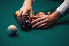 Jugar el billar Bolas de billar en la tabla de billares verde El jugador caucásico puso la bola dentro Visión desde el lado Foto de archivo libre de regalías