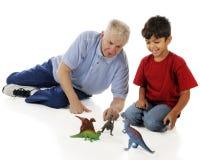 Jugar el dinosaurio con el Grandpa fotos de archivo