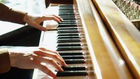 Jugar el piano El hombre joven juega un piano El pianista hermoso juega melodías Luz agradable de una ventana dentro almacen de video