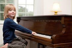Jugar el piano, instrumento del niño del muchacho Foto de archivo