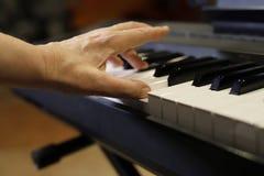 Jugar el piano, manos que juegan el piano foto de archivo