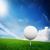 Jugar a golf. Bola en te en hierba Imagen de archivo libre de regalías