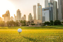 Jugar a golf en la puesta del sol La pelota de golf está en la camiseta para una pelota de golf Foto de archivo