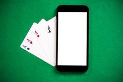 Jugar juegos y el póker del casino en el teléfono móvil imagen de archivo libre de regalías