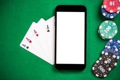 Jugar juegos y el póker del casino en el teléfono móvil fotografía de archivo