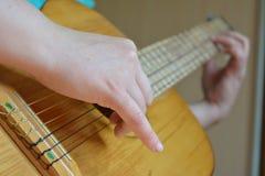 Jugar la mano del ser humano de la guitarra Fotografía de archivo libre de regalías