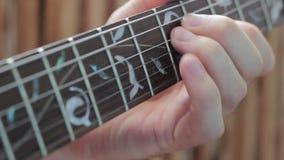 Jugar los fingeres del fingerboard de la guitarra eléctrica de su mano izquierda metrajes