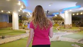 Jugar a mini golf Una mujer rubia joven toma un palillo del golf del bolso y sale almacen de video