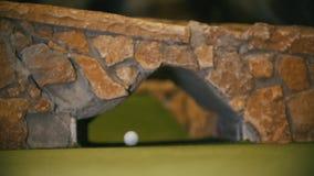 Jugar a mini golf Una pequeña bola está rodando en el campo debajo del puente metrajes