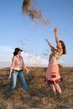 Jugar a muchachas en heno Fotos de archivo