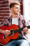 Jugar su melodía preferida Hombre joven hermoso que toca la guitarra acústica y que mira a través de la ventana Foto de archivo