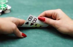 Jugar a tarjetas y salta adentro las manos Fotos de archivo