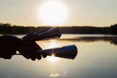 Jugar un agogo del instrumento musical en el cielo del fondo en la puesta del sol Fotografía de archivo