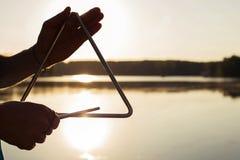 Jugar un triángulo del instrumento musical en el cielo del fondo en la puesta del sol Foto de archivo libre de regalías