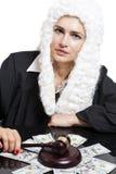 Juge corrompu de femelle comptant l'argent à la table sur le blanc photographie stock