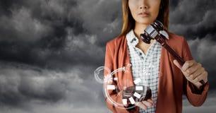 Juge féminin avec le marteau et interface blanche contre le ciel gris images stock