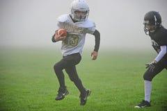 Jugend-amerikanischer Fußball in den Nebel Stockfoto