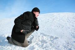 Jugend, die auf einem Knie auf Schnee sich lehnt Lizenzfreie Stockfotografie