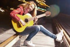 Jugend-Lebensstil-Ideen und Konzepte Junge-lächelnde kaukasische blonde Frau, welche draußen die Gitarre nachts spielt Lizenzfreie Stockfotografie