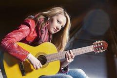 Jugend-Lebensstil-Ideen und Konzepte Kaukasische blonde Frau, welche draußen die Gitarre nachts spielt Lizenzfreie Stockfotografie