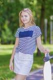 Jugend-Lebensstil-Konzepte Blonde kaukasische Jugendliche, die mit langem Skateboard im grünen Wald aufwirft Stockfoto