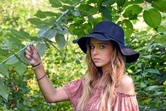 Jugend mit Mädchen des schwarzen Hutes im Holz Stockfotos