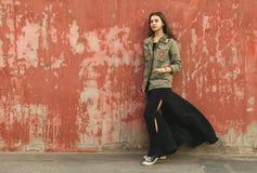 Jugend recht weiblich auf Straße nahe roter Wand Lizenzfreie Stockfotos