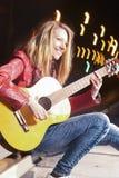Jugend-Straßen-Leben-Konzepte Porträt des lächelnden kaukasischen blonden Mädchens, welches die Gitarre draußen auf Straße spielt Lizenzfreie Stockfotos