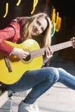 Jugend-Straßen-Leben-Konzepte Positives kaukasisches blondes Mädchen, welches die Gitarre draußen auf Straße spielt Lizenzfreies Stockbild